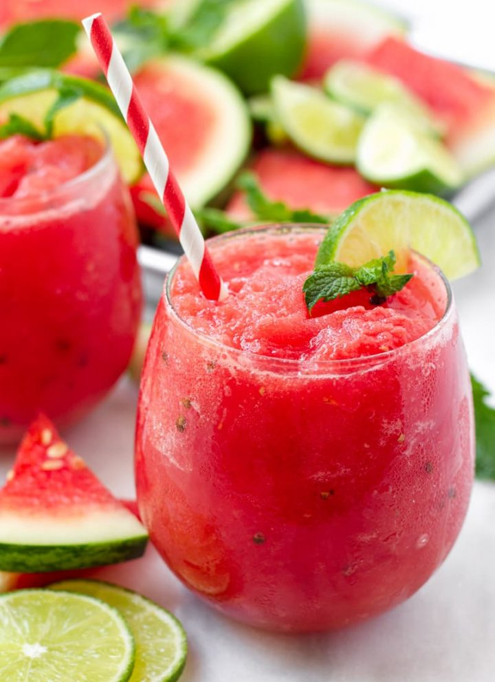 Red watermelon slush with red and white paper straw, plus lime and mint garnish