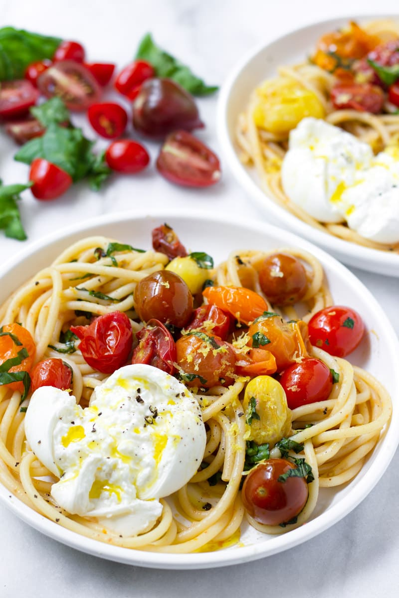 Two plates with fresh tomato sauce pasta and fresh burrata drizzled with olive oil