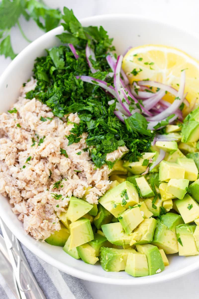 Bowl with canned tuna, diced avocado, chopped parsley, and lemon