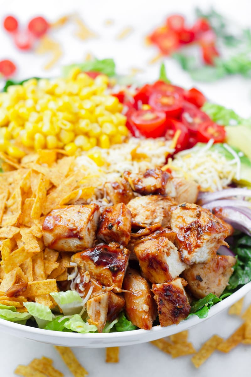close up of grilled chicken salad, corn, tomatoes, tortillas chips, and bbq sauce