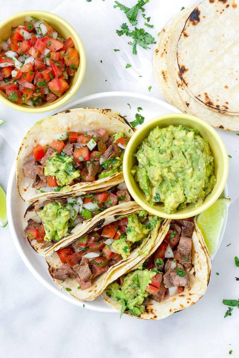 Four carne asada tacos with guacamole and pico de gallo