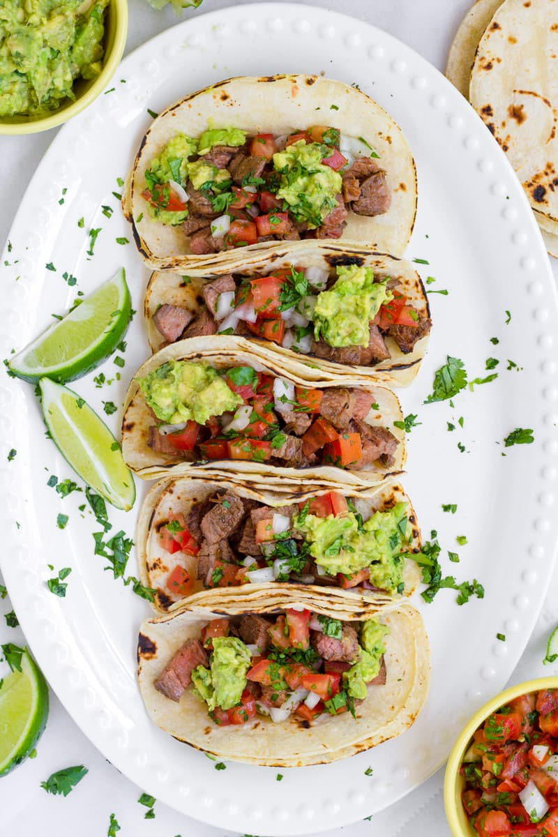 Top view of five carne asada tacos on a oval platter