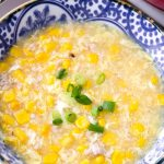 close up of bowl with corn soup and green onion garnish