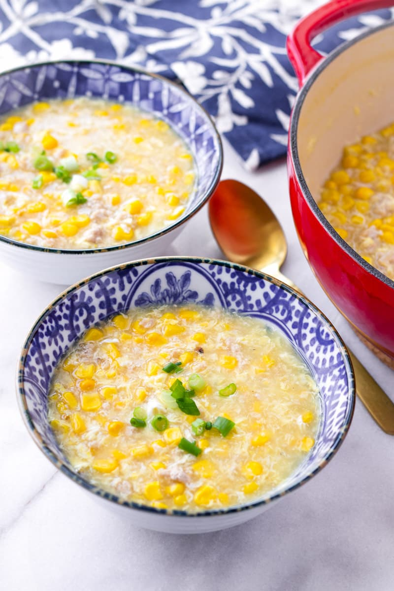 Two blue bowls with Chinese chicken soup with corn