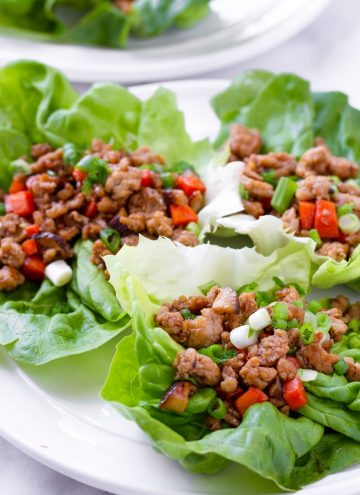 Three Asian lettuce wraps on white plate