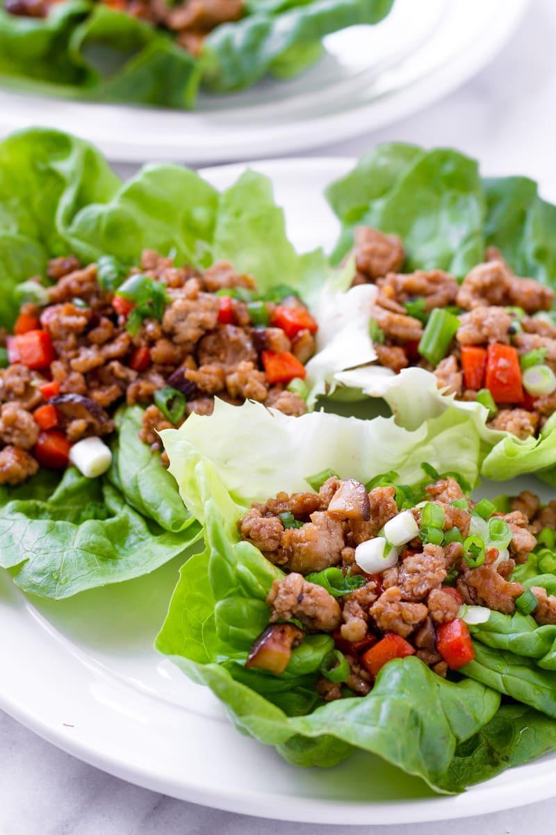 Three Asian lettuce wraps on white plate