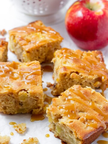 Four slices of fresh apple cake with caramel drizzle and a honeycrisp apple in the back