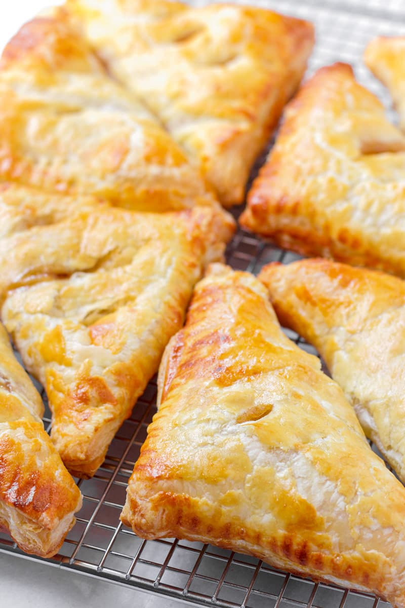 Flaky and golden brown apple turnovers on a cooling rack
