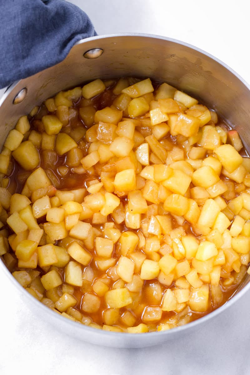 pot with cooked diced apple filling and a blue towel hanging on handle