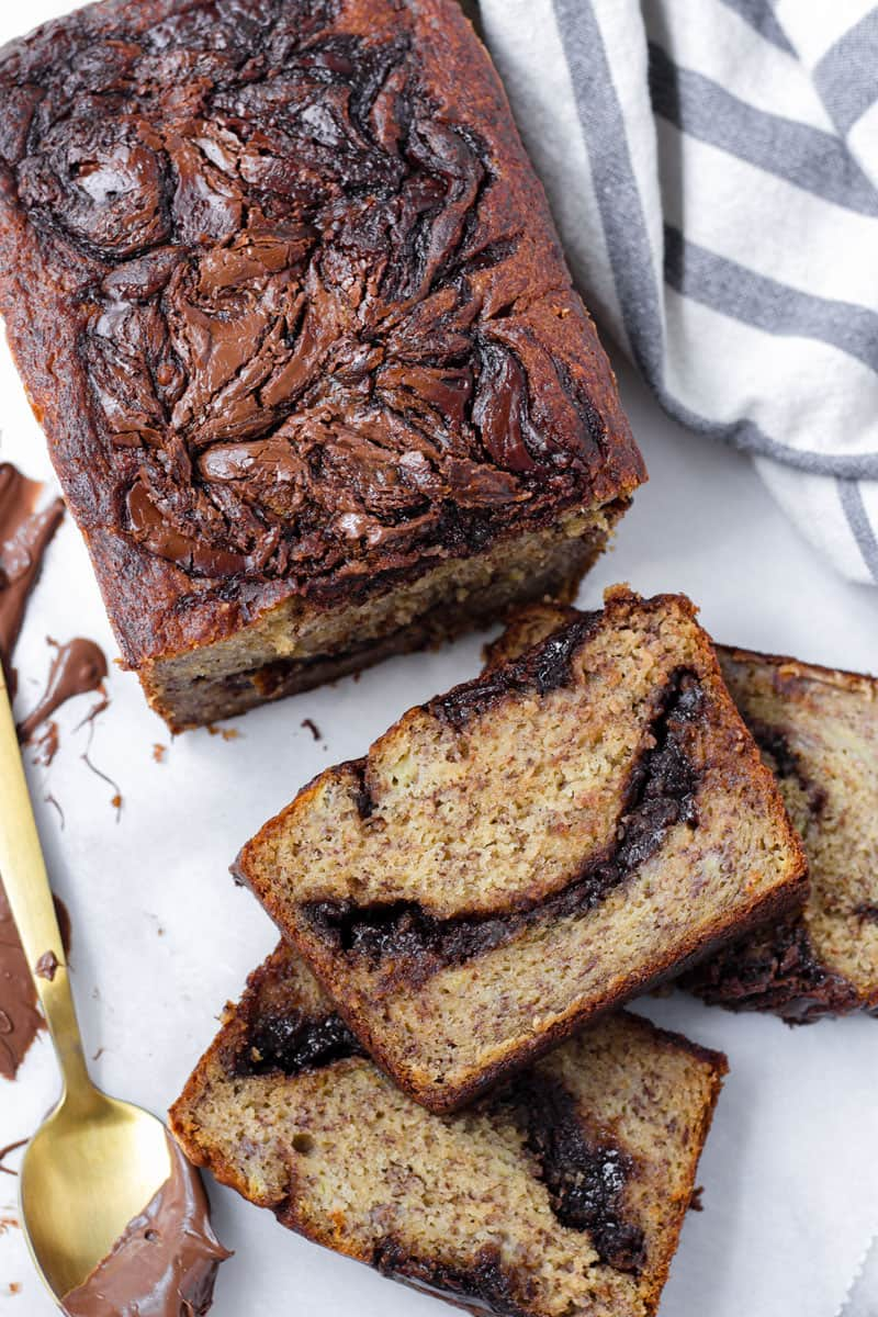 top view hazelnut chocolate banana bread with striped towel and golden spoon