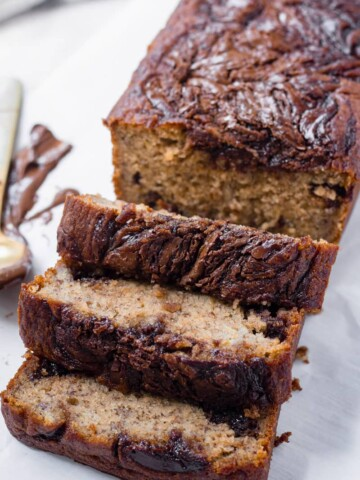 sliced loaf of nutella banana bread with spoon in background
