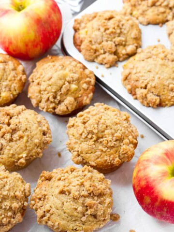 a few muffins arranged on surface, two red apples, and muffins in pan