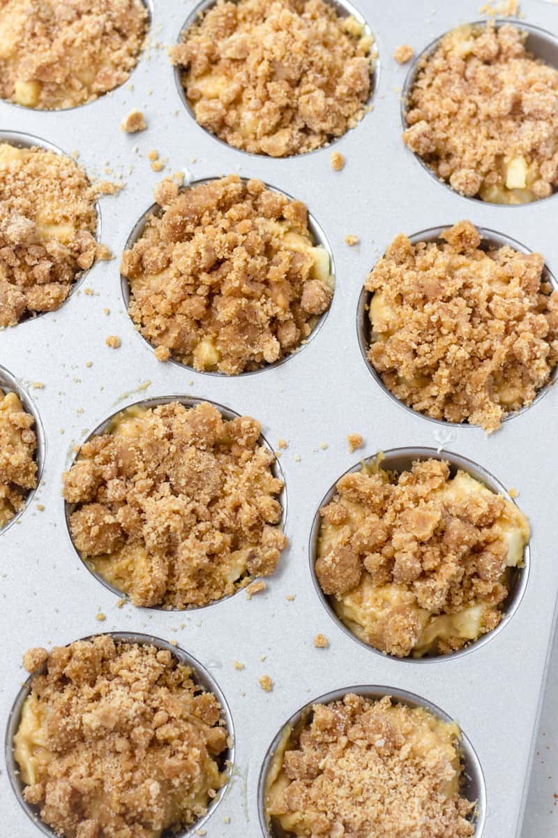 muffin pan filled with prepared batter and crumb topping