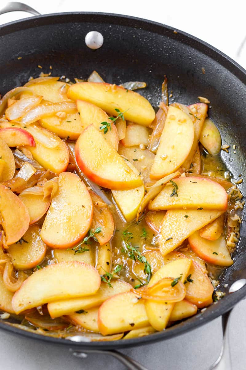cooked sauce made with apple slices, yellow onions, herbs, and apple cider on skillet