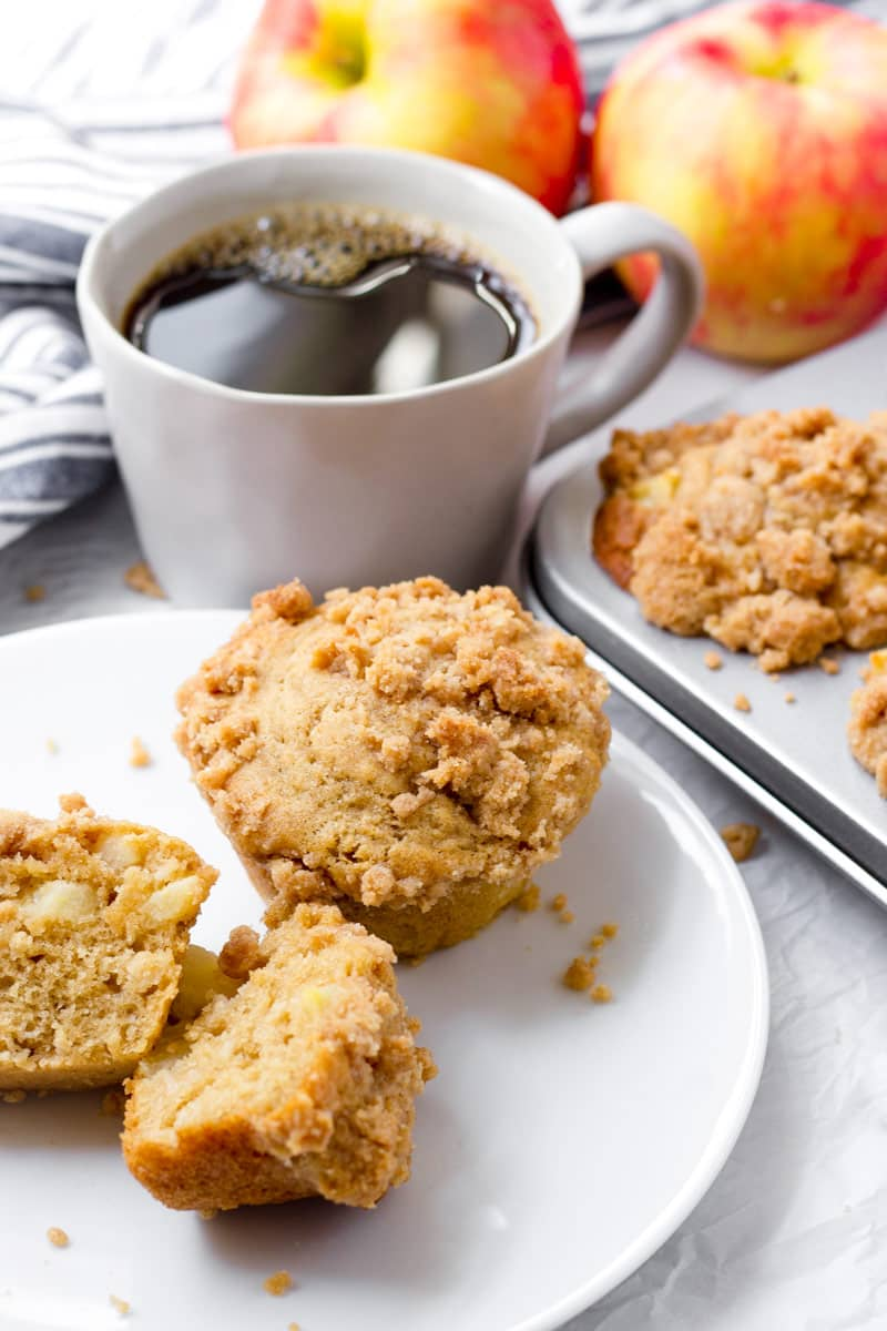 muffins on plate with a cup of coffee, and two apples and a towel in background