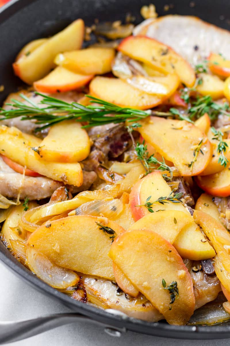 close up of cooked pork chops topped with cooked apples and onions sauce