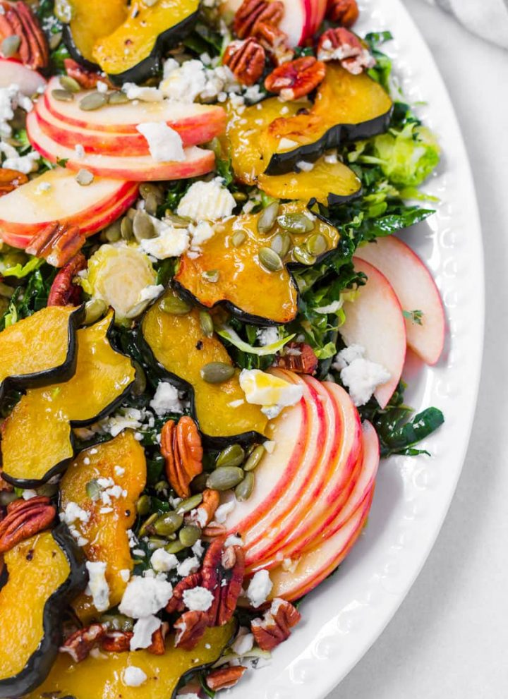 Half view of a fall themed salad platter made of apples, roasted acorn squash, kale, cheese, and nuts