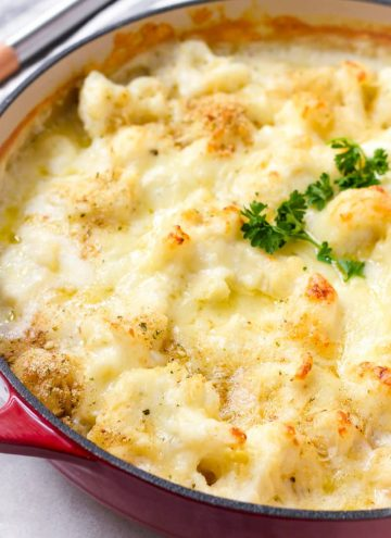 baked and golden brown cauliflower with cheese in a red Dutch oven pot