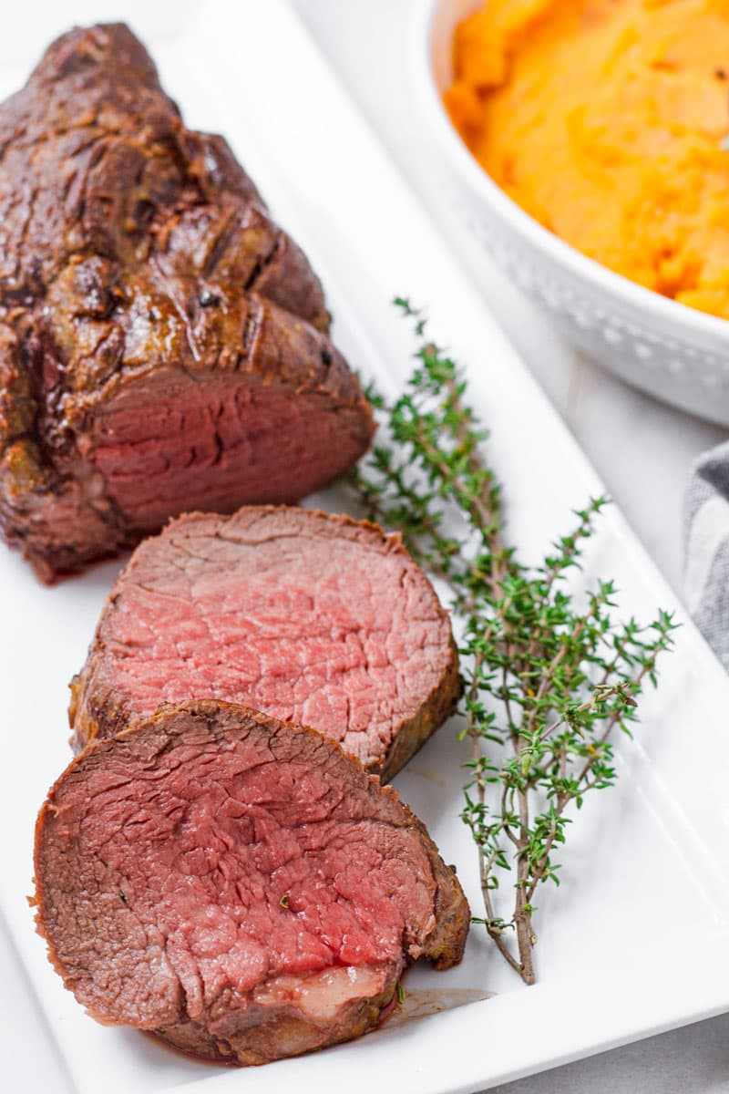 sliced roast beef tenderloin on a rectangular plate and with thyme garnish