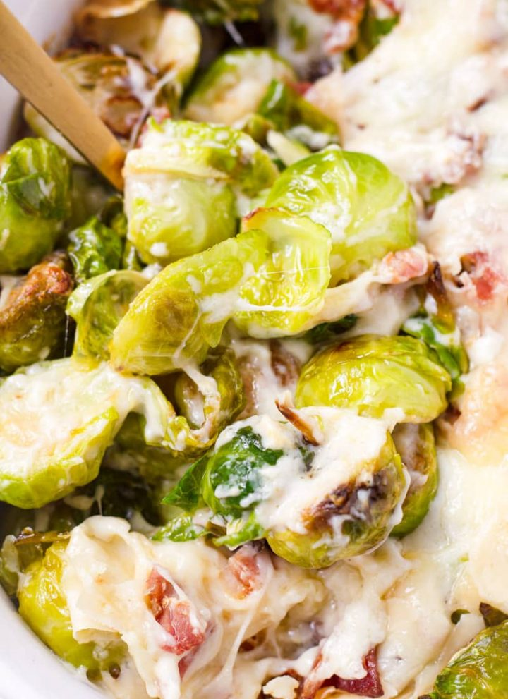 Close up of cheese baked brussels sprouts being scooped up with a spoon