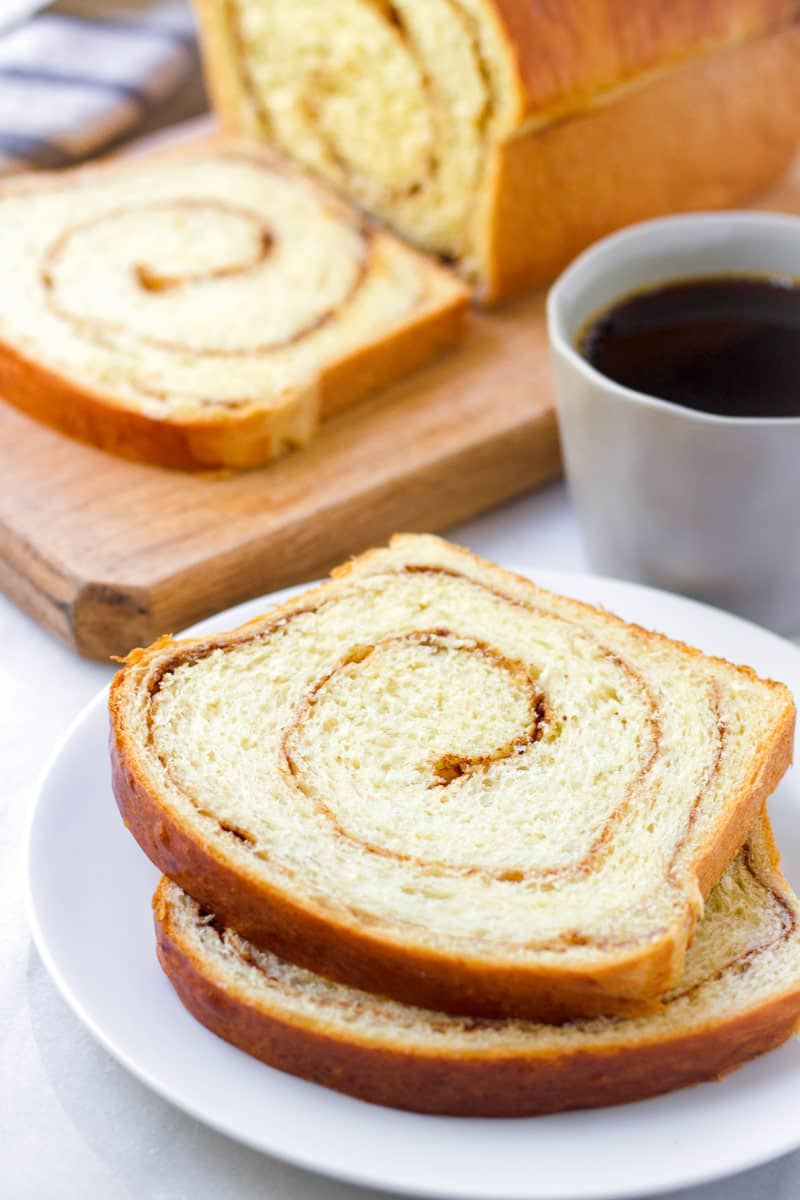 slices of cinnamon swirl bread with bread loaf and coffee in the background
