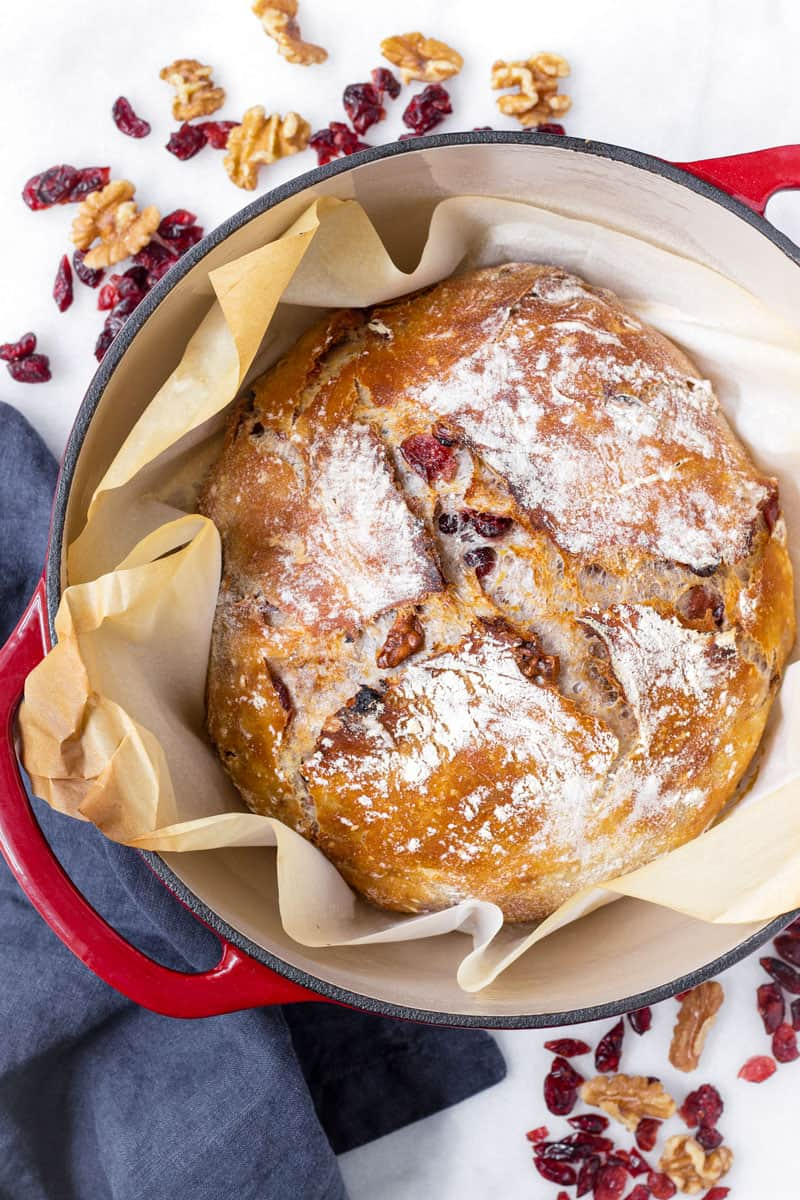 baked crusty cranberry nut bread in a red Dutch oven pot