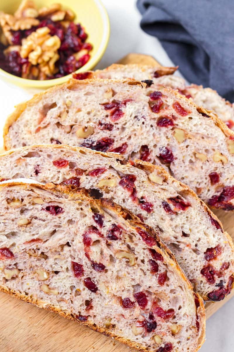 Sliced artisan cranberry nut bread on wooden board