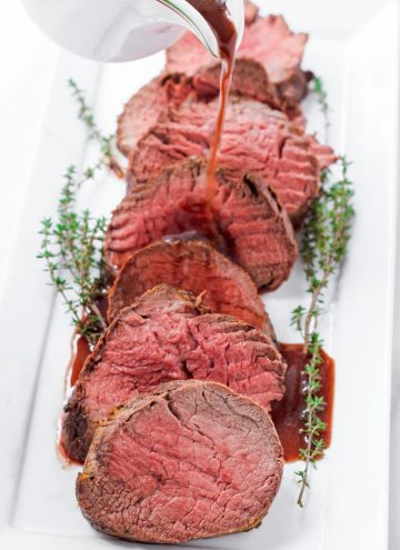 red wine sauce being poured onto sliced roast beef medallions