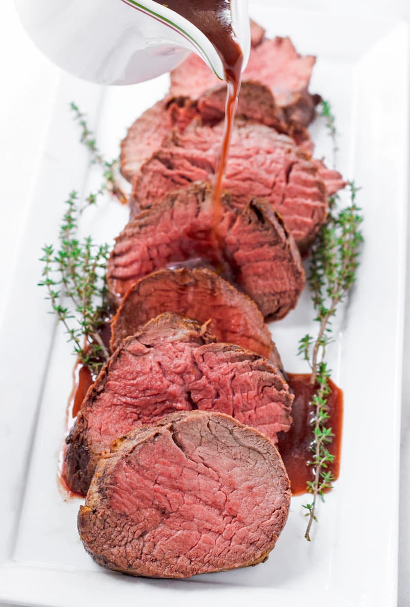 red wine sauce being poured onto sliced beef medallions