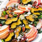 salad platter made of apples, roasted acorn squash, kale, pecans, and pumpkin seeds