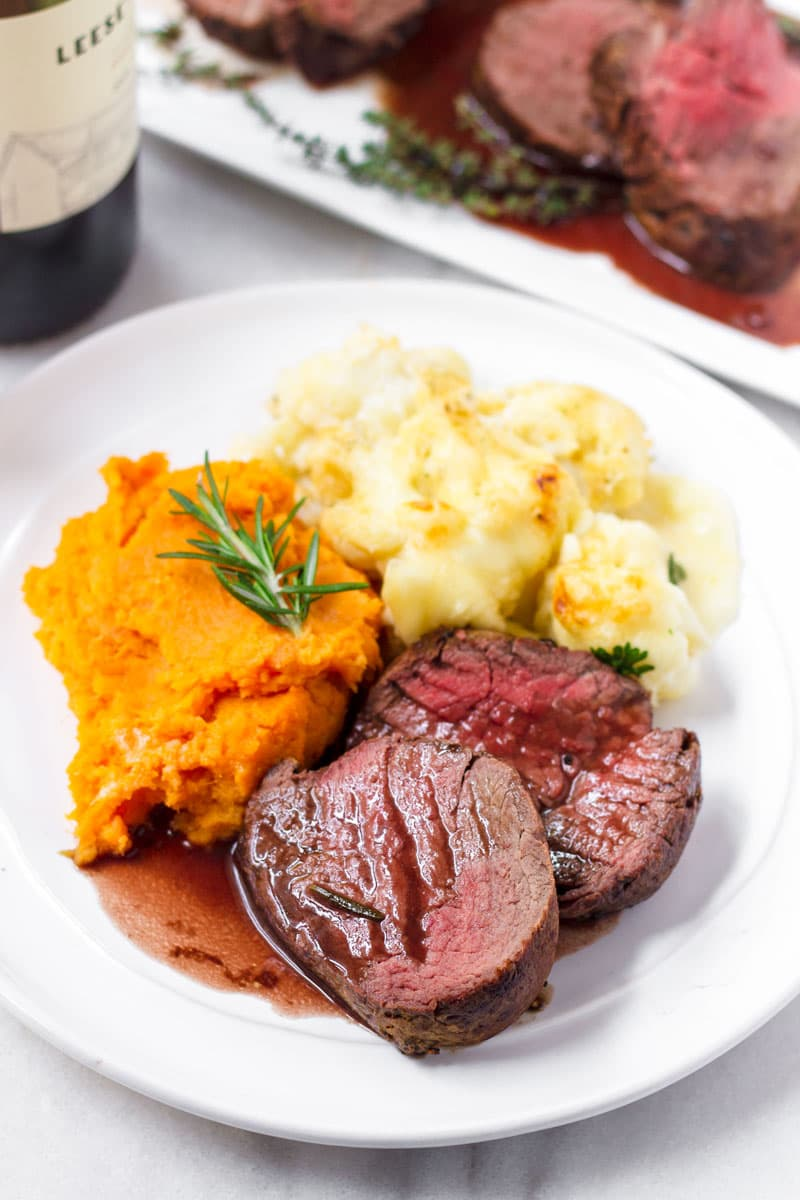 a platter with mashed sweet potatoes, cauliflower, and sliced beef tenderloin served with red wine sauce