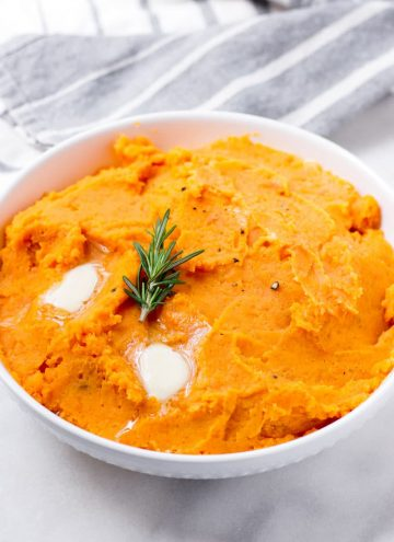 white bowl with prepared mashed sweet potatoes with melty butter and rosemary on top