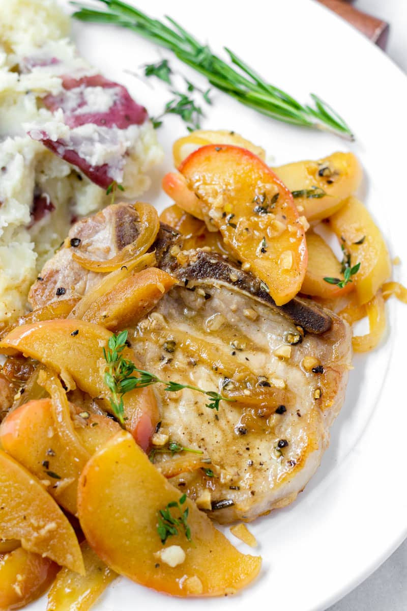 A cooked bone-in pork chop served with cooked apples, onions, and mashed potatoes on the side