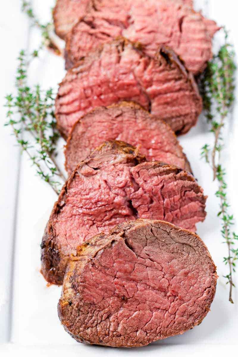 sliced medallions of beef tenderloin on a rectangular plate and cooked to medium doneness