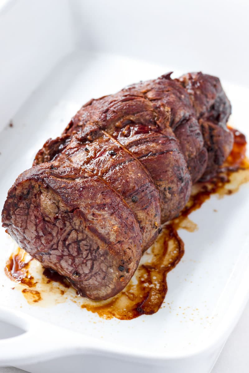 Whole cooked beef loin tied with kitchen twine on a white baking pan