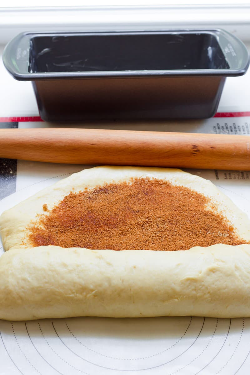 dough with cinnamon and sugar filling being rolled for pan