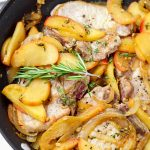 cooked pork chops with onions, apples, and rosemary on a stainless steel pan