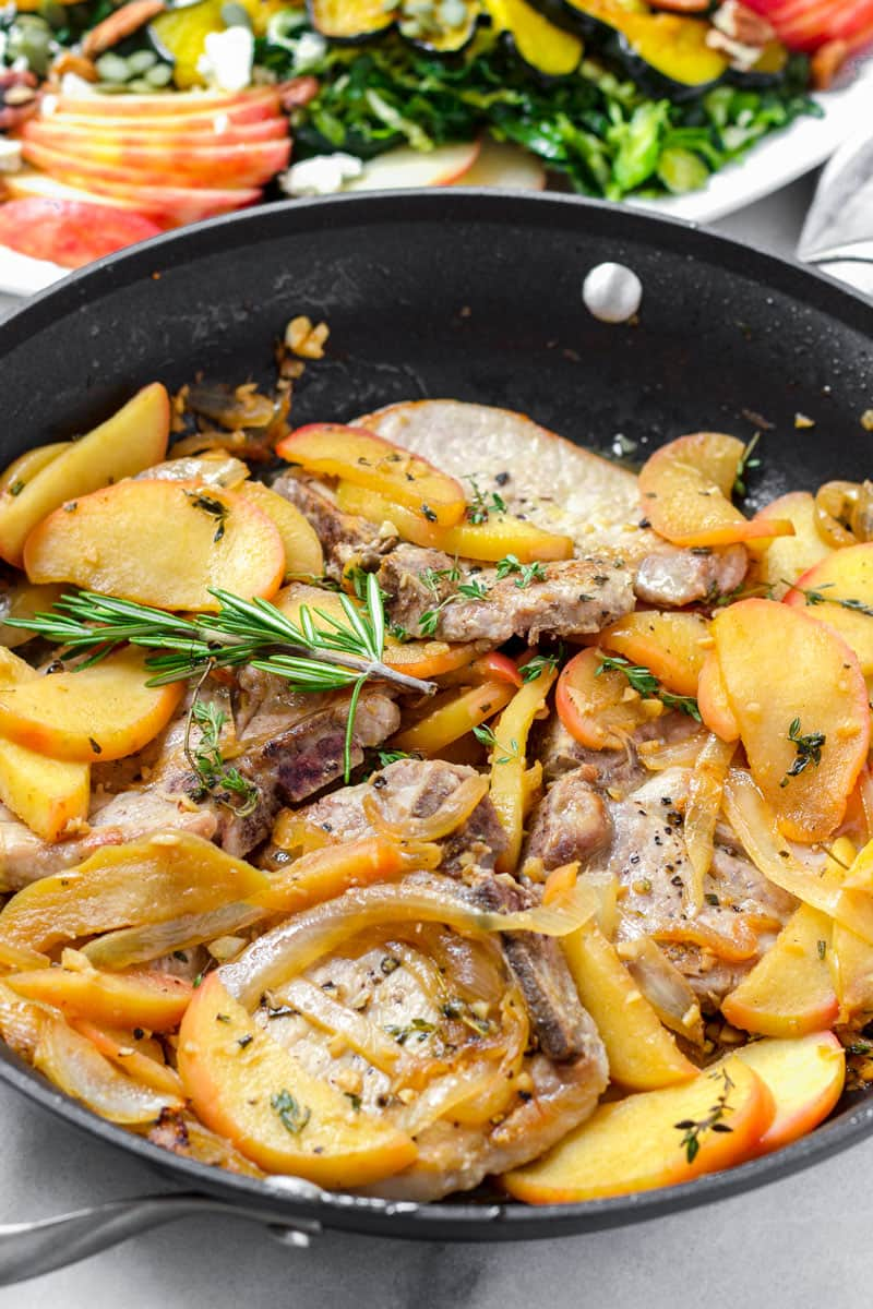 skillet pork chops with cooked apples and onions, garnished with rosemary sprig