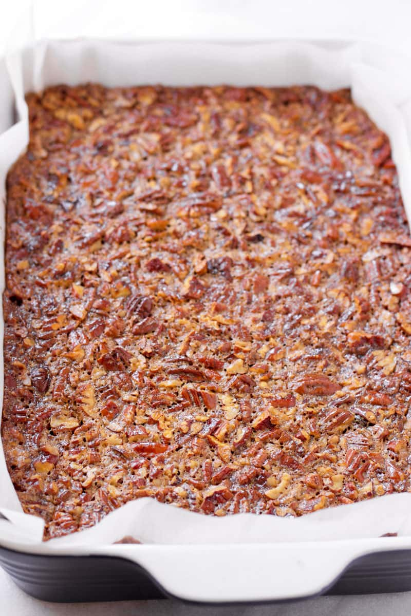 A 9 by 13 baking pan with baked pecan pie bar on parchment paper