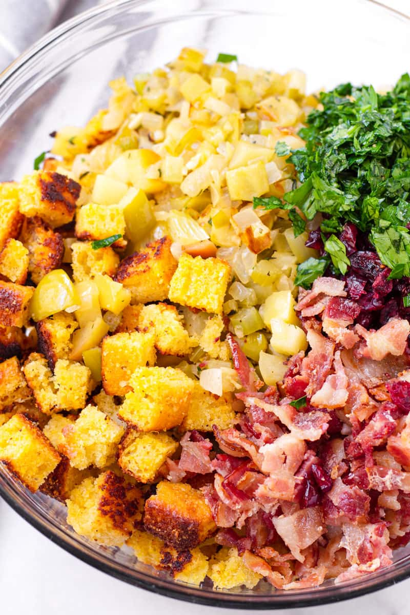 large glass bowl with cubed cornbread, bacon, cooked onions and garlic, chopped parsley, and dried cranberries