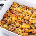 Baked stuffing on a large rectangular baking dish and next to a grey napkin