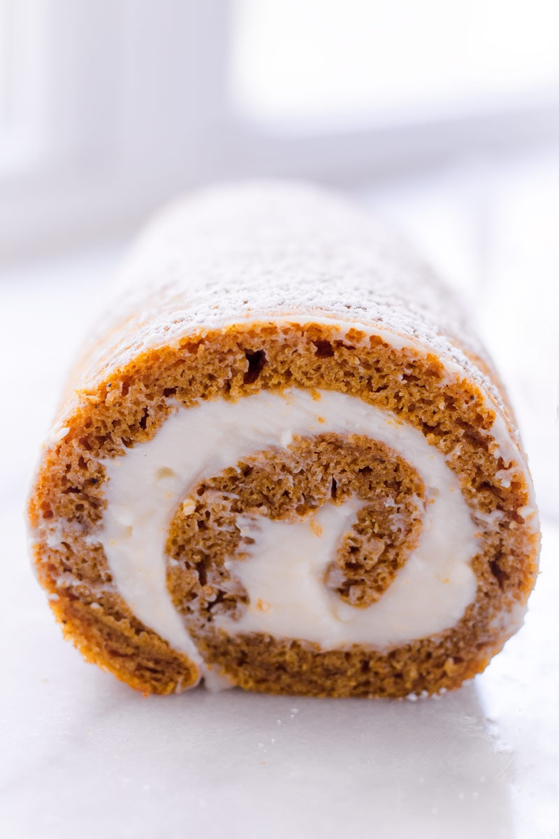 straight view of a pumpkin roll filled with cream cheese frosting