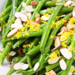 close up of green bean salad tossed with lemon dressing, topped with lemon zest and almonds