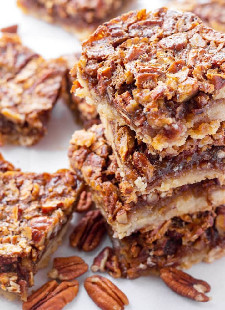 stacked pecan pie bars with a few pecans next to them