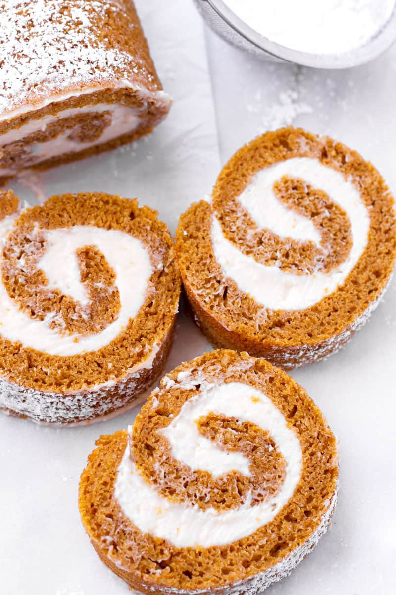 three slices of pumpkin roll laying on parchment paper