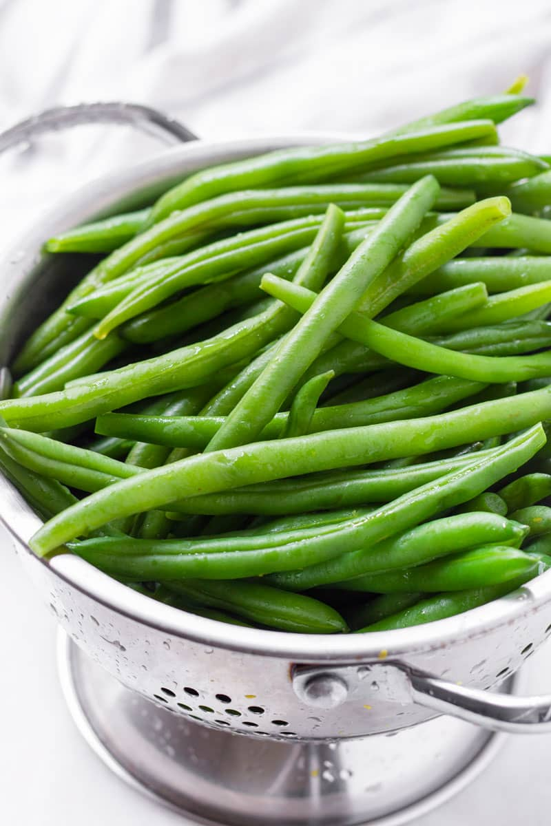 Rinsed uncooked green beans in a stainless steel colander