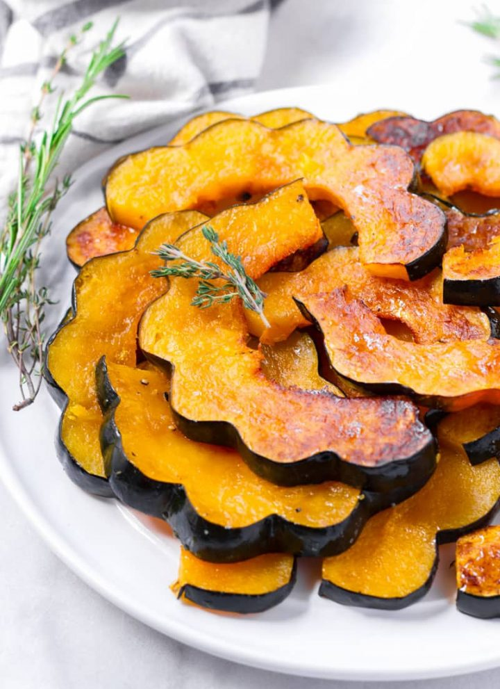 maple roasted acorn squash slices piled up on plate and with rosemary garnish
