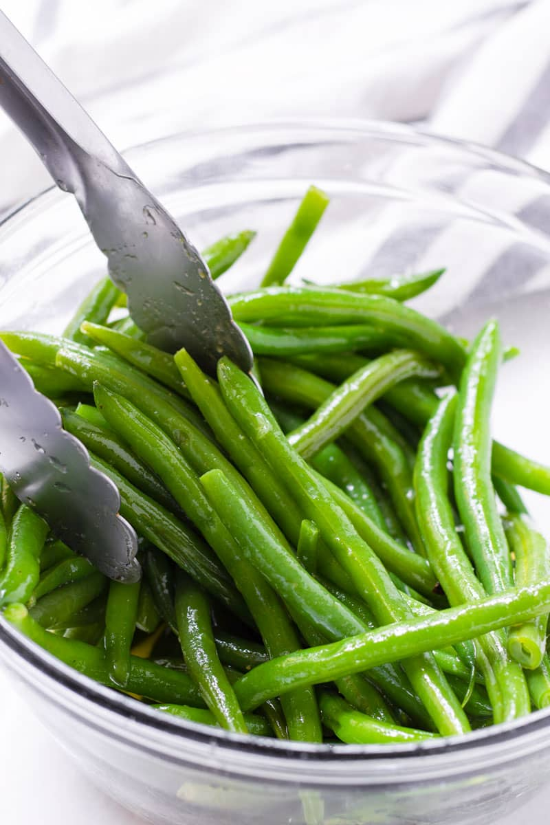 Green beans with dressing being tossed with tongs in a glass bowl