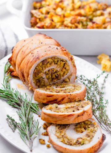 cooked roasted turkey roll with three slices on an oval plate, garnished with thyme and rosemary