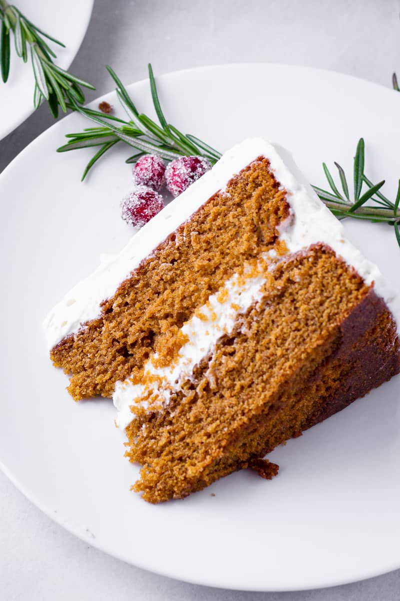 One slice of gingerbread cake on a plate with rosemary and cranberry decorations